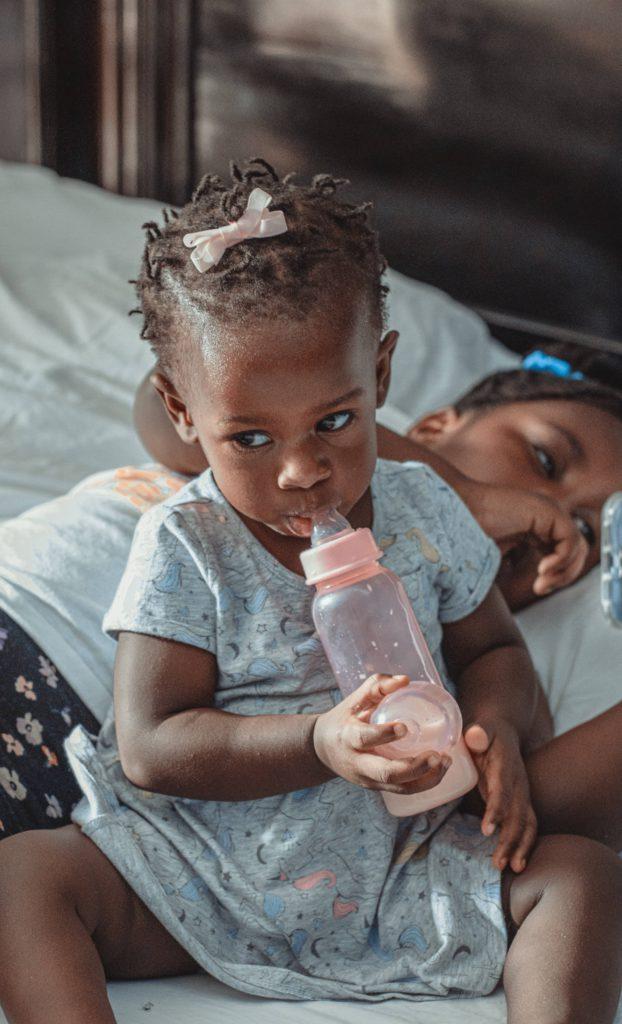 Baby girl suckling feeder