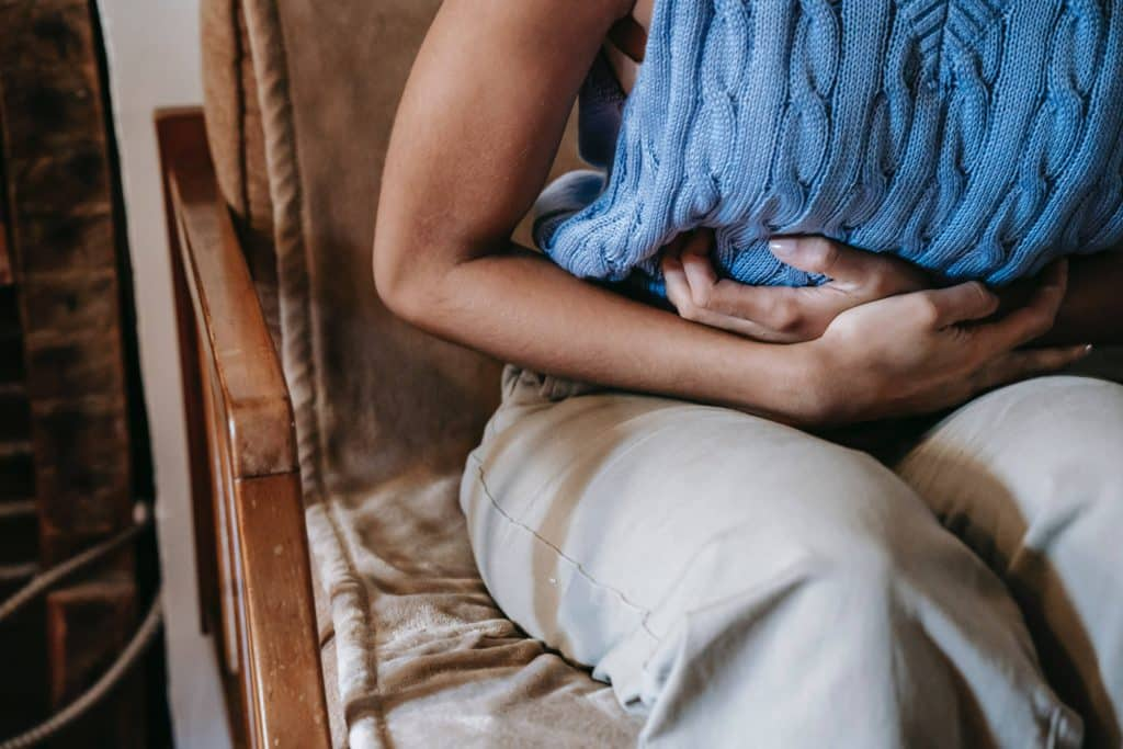 woman holding her breast in pain