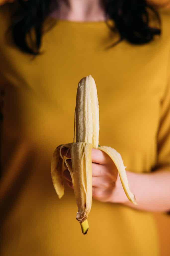 woman trying to eat banana