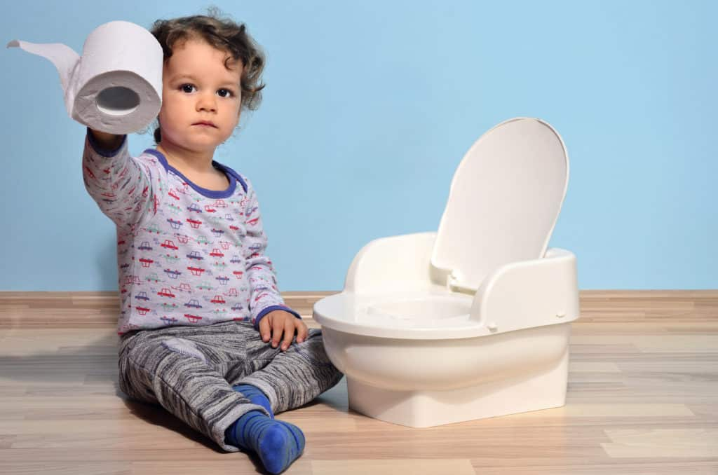 baby holding tissue and sitting beside a potty
